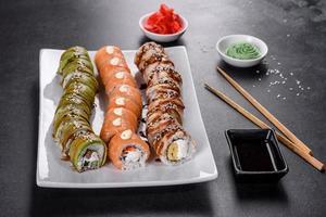 Rollos de sushi frescos y sabrosos dispuestos en forma de dragón con jengibre y wasabi foto