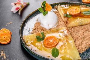Deliciosos panqueques frescos en un plato con salsa dulce y helado decorado con menta foto