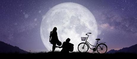 silueta en el paisaje nocturno de pareja o bailando y cantando en la montaña foto