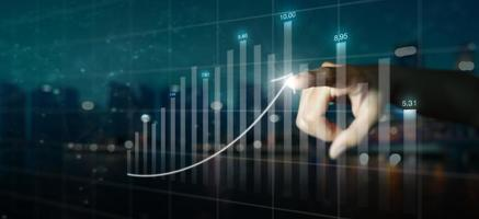 Double exposure of business mans hand pointing to arrow graph and chart photo