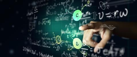 Hand on science formula and math equation on abstract blackboard photo