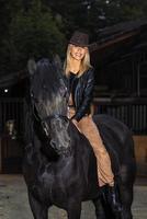 Hermosa joven montar su caballo marrón durante la equitación foto