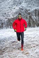 Entrenamiento de un corredor de pista en el frío en la helada. foto