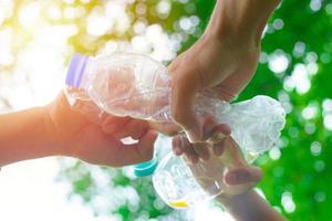 Volunteer man's hand picking up plastic bottle photo
