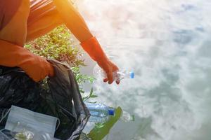 Man picking up a bottle plastic in the lake photo