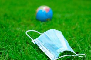 Medical mask in fresh, green spring grass photo
