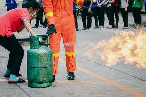 capacitación de los empleados sobre extinción de incendios, cierre la válvula del tanque de gas que se enciende. foto