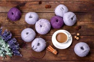 Enredos de hilos de lana y radios con una taza de café y azúcar sobre un fondo de madera foto