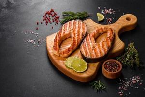 Fresh cooked delicious salmon steak with spices and herbs baked on a grill photo