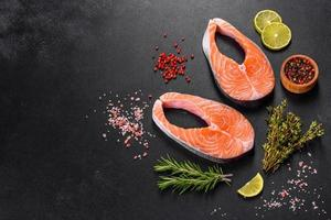 Fresh raw salmon steak with spices and herbs prepared for grilled baking photo