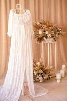 Decoraciones de hermosas flores secas en un jarrón blanco sobre un fondo de tela beige foto
