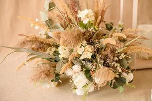Decorations from dry beautiful flowers in a white vase on a beige fabric background photo