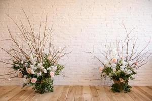 Decoraciones de ramas con hermosas flores rosas y blancas en la canasta con el telón de fondo de una pared de ladrillo blanco. foto