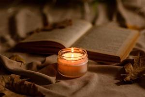 A burning candle on a wooden table in front of a book in a half-mast photo