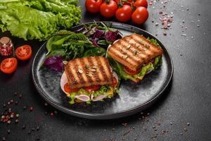 delicioso sándwich con tostadas crujientes, jamón, lechuga y tomates foto