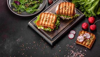 Delicious sandwich with crisp toast, ham, lettuce and tomatoes photo