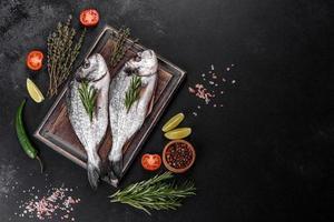 Raw dorado fish with spices cooking on cutting board. Fresh fish dorado photo