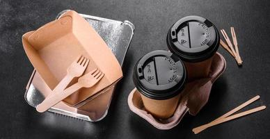 Disposable dishes made of environmentally friendly brown cardboard on a dark background photo