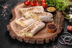 Delicious fresh shawarma with meat and vegetables on a dark concrete table photo