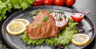 Delicioso y jugoso filete de atún a la parrilla con especias y hierbas. foto