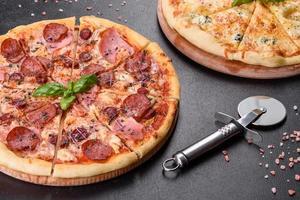 Deliciosa pizza recién horneada con tomates, salami y tocino sobre un fondo de hormigón oscuro foto