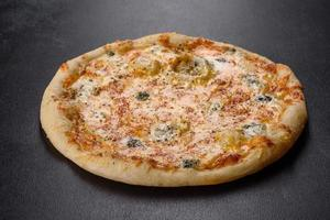 Tasty fresh oven pizza with tomatoes, cheese and mushrooms on a dark concrete background photo