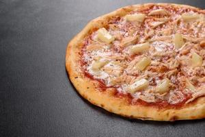 Tasty fresh oven pizza with tomatoes, cheese and pineapple on a dark concrete background photo