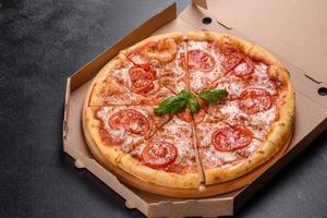 Sabrosa pizza recién horneada con tomate, queso y albahaca sobre un fondo de hormigón foto