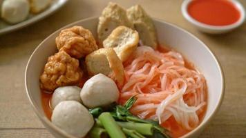små platta risnudlar med fiskbollar och räkor i rosa soppa, yen ta fyra eller yen ta fo - asiatisk matstil video