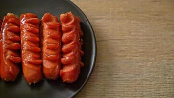 Deep fried sausage skewer on black plate video