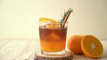 A glass of iced americano black coffee and layer of orange and lemon juice decorated with rosemary and cinnamon video