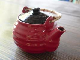 Tetera china roja sobre una mesa de madera foto