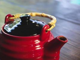 Tetera china roja sobre una mesa de madera, close-up foto