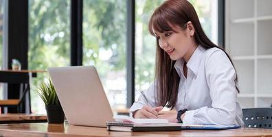 Joven empresaria asiática sentada y feliz trabajando con ordenador portátil foto