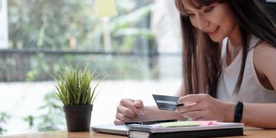 Mujer sonriente utilice el teléfono móvil para comprar en línea con tarjeta de crédito foto