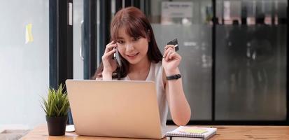 mujer sonriente sentada oficina hablando por teléfono móvil foto