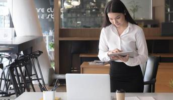 Portrait of young businesswoman standing at her desk using a laptop photo