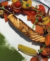 Roasted salmon steak with vegetables garnish photo