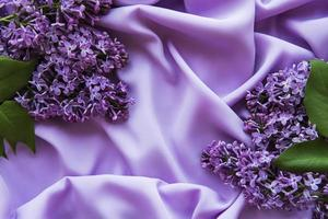 Lilac flowers on a background of lilac satin photo