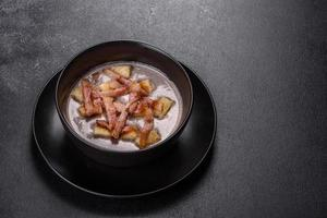 Fresh delicious hot puree soup with mushrooms and bacon in a black plate photo