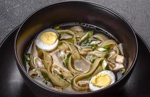 Deliciosa sopa caliente fresca con fideos y huevo de codorniz en una placa negra foto