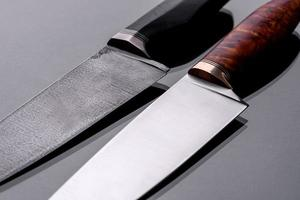A large handmade hunting knife lying on a dark background photo