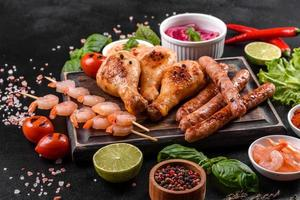 Composition of sausages, chicken, pork and shrimp prepared on grill, as well as vegetables prepared on grill with spices and herbs photo