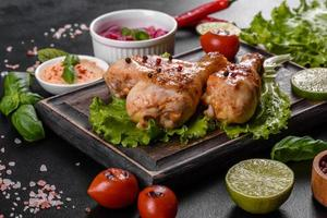 Tasty grilled chicken legs with spices and herbs on a wooden board on a dark concrete background photo
