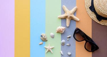 Glasses and hat with shells and sea stars on a colored background photo
