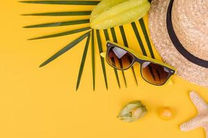 Fruit carambol, beach accessories and foliage of a tropical plant on colored paper photo
