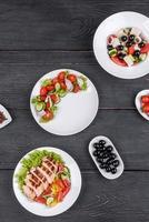 tres deliciosas ensaladas frescas con pollo, tomate, pepino, cebolla y verduras con aceite de oliva foto