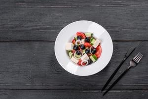 deliciosa ensalada griega fresca con tomate, pepino, cebolla y aceitunas con aceite de oliva foto