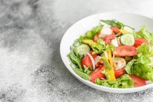 deliciosa ensalada fresca con pollo, tomate, pepino, cebolla y verduras con aceite de oliva foto