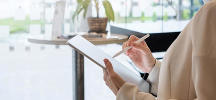 Mujer sosteniendo tableta digital con pantalla en blanco y lápiz óptico foto